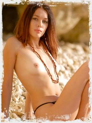 Cute brunette in a leopard negligee undressing on the beach.